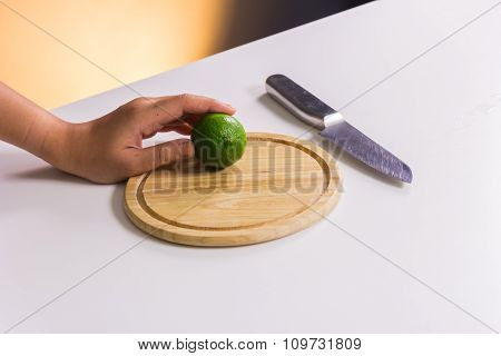 Fresh And Sour Green Lime Or Lemon, Half Cut With Knife On Chopping Board