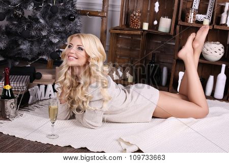 beautiful young woman with blond hair and charming smile wears cozy knitted cardigan