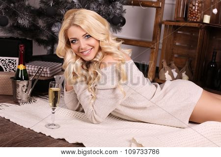 Beautiful Blond Woman With Champagne Posing Beside Christmas Tree