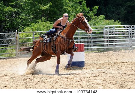 Young adult woman galloping through a turn in a barrel race