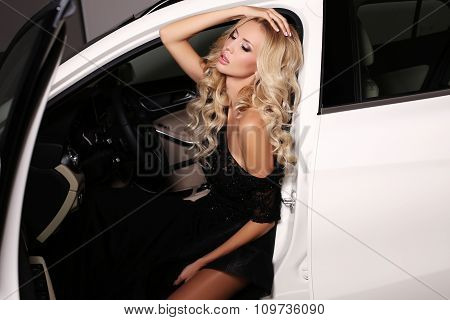 Woman With Long Blond Hair Wears Luxurious Dress,posing In White Car
