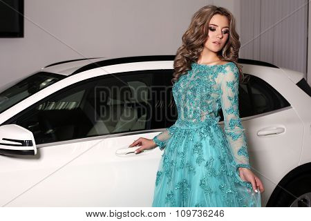 Woman With Long Blond Hair Wears Luxurious Dress,posing Beside White Car