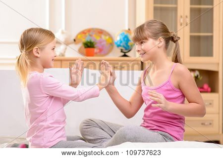 Positive little sisters clapping their hands