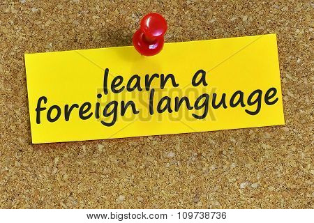Learn A Foreign Language Word On Yellow Notepaper With Cork Background