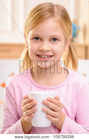 Nice little girl drinking tea