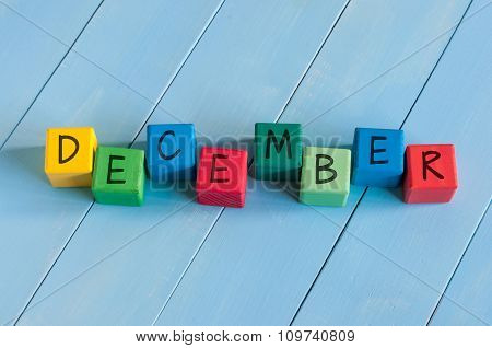 Word December On child's toy cubes on wooden rural  background.