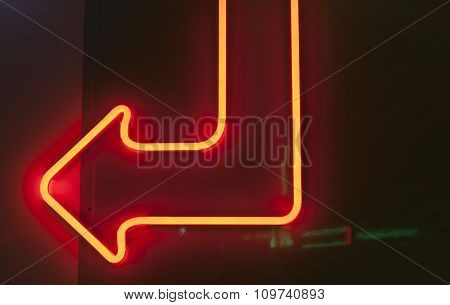 Red Neon Arrow On Dark Background.
