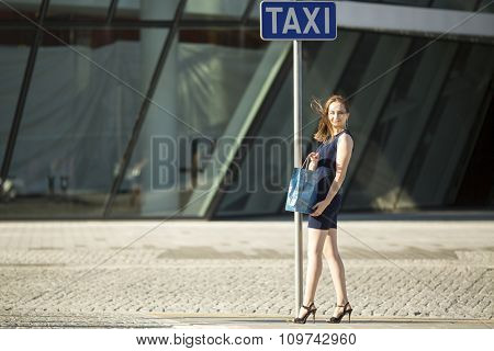 Young fashionable girl after shopping standing on the street.