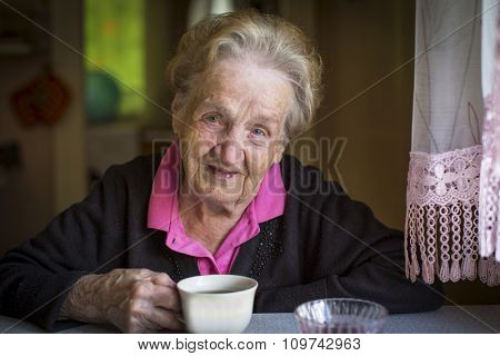 Portrait of elderly woman drinking tea.