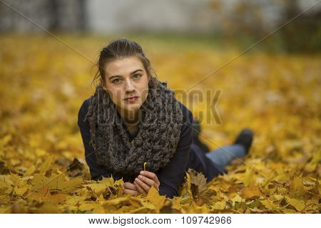 Cute girl lying on leaves in autumn Park.