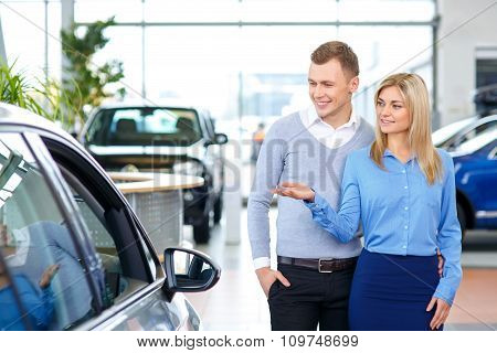 Pleasant man choosing car in auto show