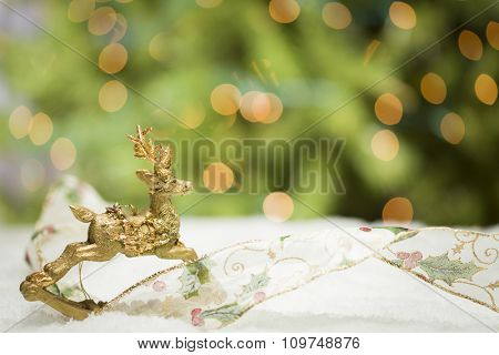 Decorative Christmas Reindeer Ornament and Ribbon on Snow with Tree and Lights Background.