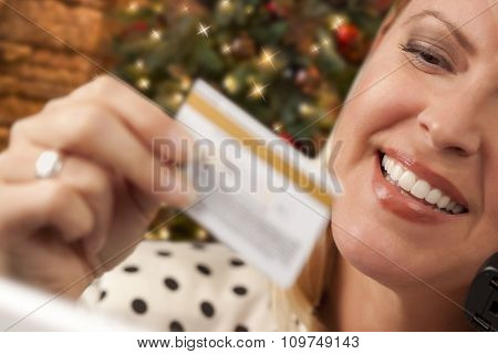 Beautiful Woman on the Phone Holding Her Credit Card In Front of Christmas Tree and Laptop Computer.