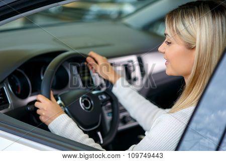 Nice woman choosing a car in auto show