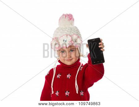 Little Girl In Warm Hat And A Red Sweater Shows Smartphone