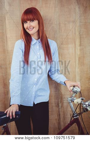 Smiling hipster woman with her bicycle against wooden background