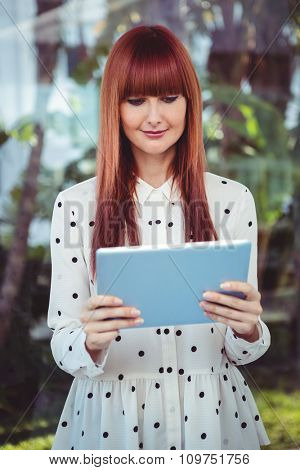 Attractive hipster woman using tablet in the garden