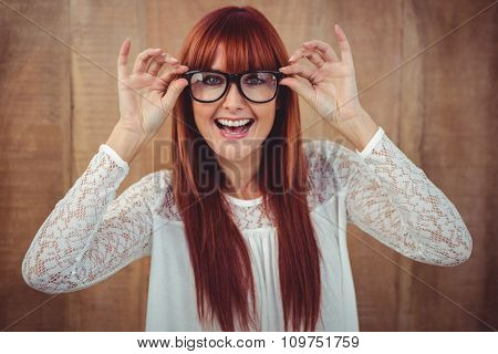 Smiling hipster woman posing face to the camera against wooden background