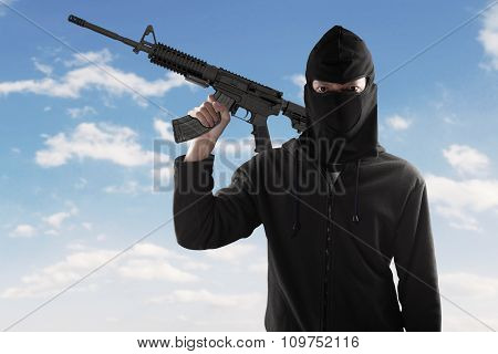 Terrorist With Rifle And Mask Under Blue Sky