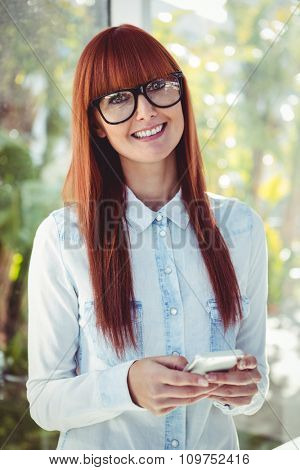 Smiling hipster woman with fringe using smartphone