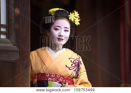 KYOTO, JAPAN - NOVEMBER 28, 2015: A woman dressed as a traditional Maiko looks out of a temple doorway.
