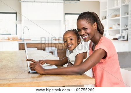 Cute daughter using laptop at desk with mother in living room