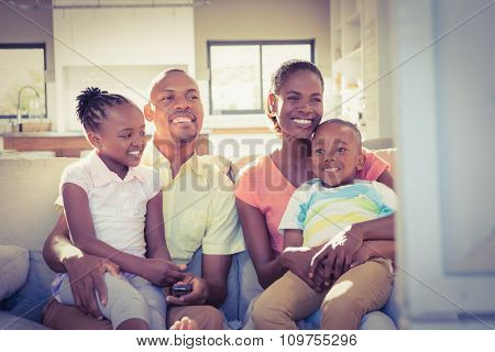 Portrait of a family of four watching tv in living room