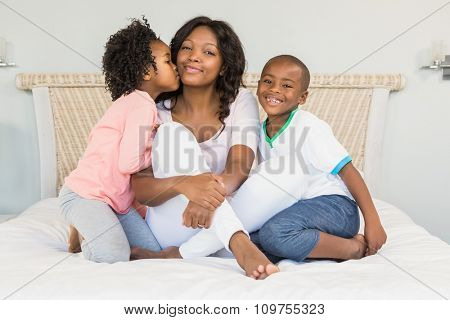 Mother and children sitting on bed at home