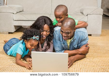 Happy family lying on the floor using laptop in the living room