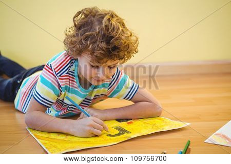 Boy lying on the ground colouring his picture