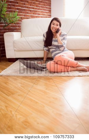 Asian woman using phone on floor at home in the living room