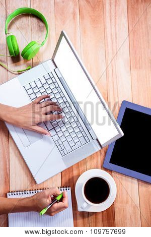 Overhead of feminine hand typing on laptop and taking notes with stuff on desk