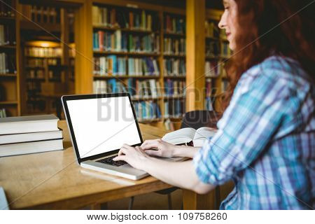 Mature student studying in library with laptop at the university