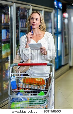 Thoughtful woman at the supermarket holding list and cart
