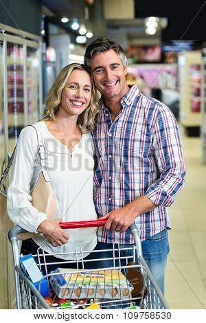 Smiling couple holding cart in the supermarket