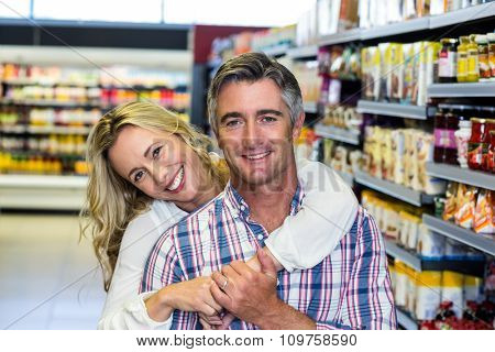 Portrait of happy couple hugging at supermarket