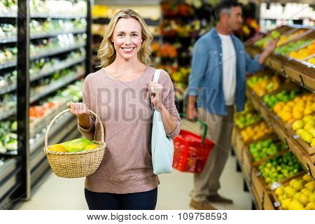 Pretty blonde woman holding vegetables basket in supermarket