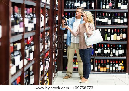 Smiling couple looking at bottle of wine at supermarket
