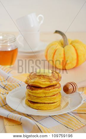 Pumpkin pancakes on white plate with butter and honey