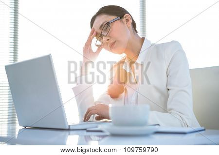 Stressed businesswoman at laptop at the desk in work