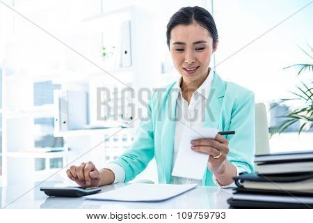 Focused businesswoman working hard with credit card at the desk in work