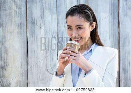 Smiling businesswoman with take-away coffee against wooden background
