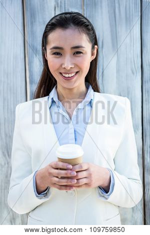 Portrait of smiling businesswoman with take-away coffee against wooden background