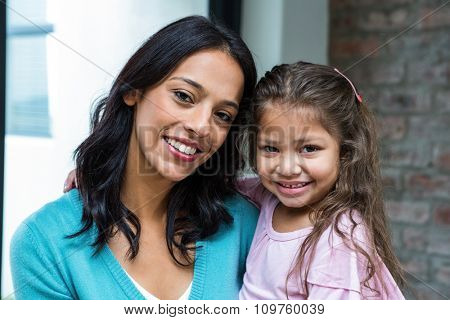 Portrait of smiling mother and daughter in living room