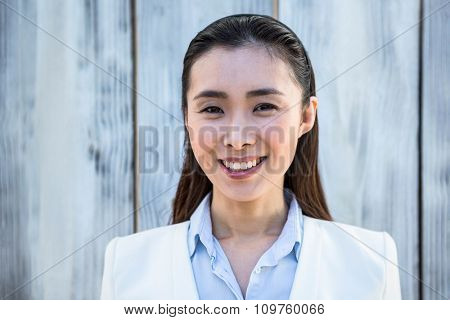 Portrait of smiling businesswoman against wooden background