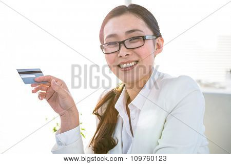 Smiling businesswoman using a credit card at her desk