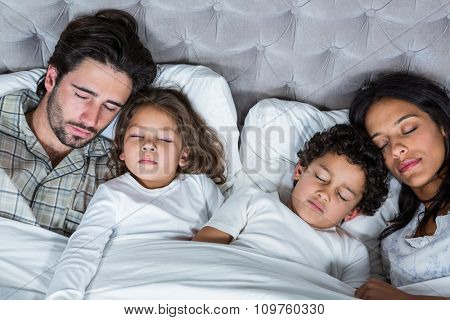 Happy family sleeping together in bed