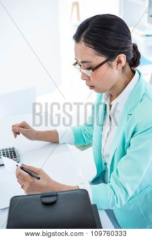 Business woman taking down notes at the desk in work