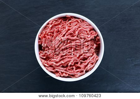 Fresh raw minced beef on old blue stone background