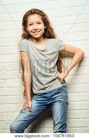 Joyful teen girl in casual clothes stands by the brick wall. Active lifestyle. Studio shot.